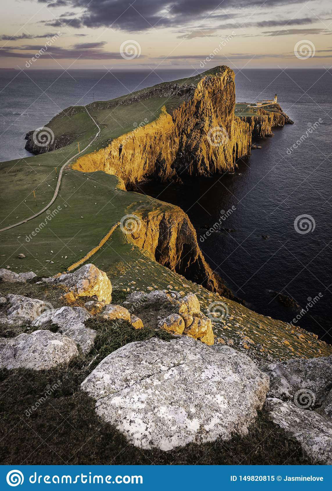 Neist Point, famous landmark with lighthouse on Isle of Skye, Scotland lit by setting sun