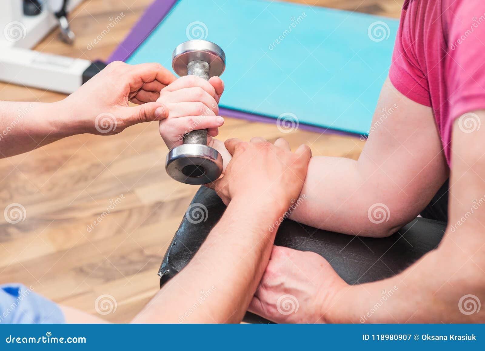 Nenhuma mulher idosa da cara que faz o active, trabalhando com o peso guiado pelo fisioterapeuta no centro de reabilitação do hos