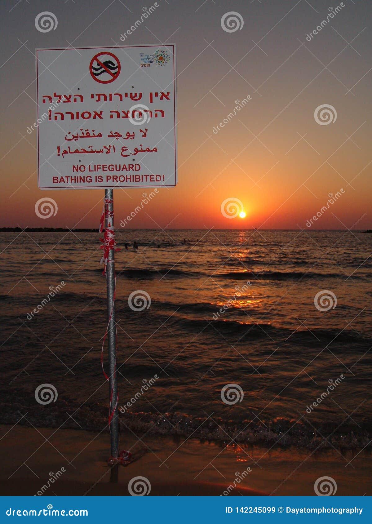Nenhuma salva-vidas, sinal proibido nadador em uma praia de Tel Aviv em morno, por do sol do verão