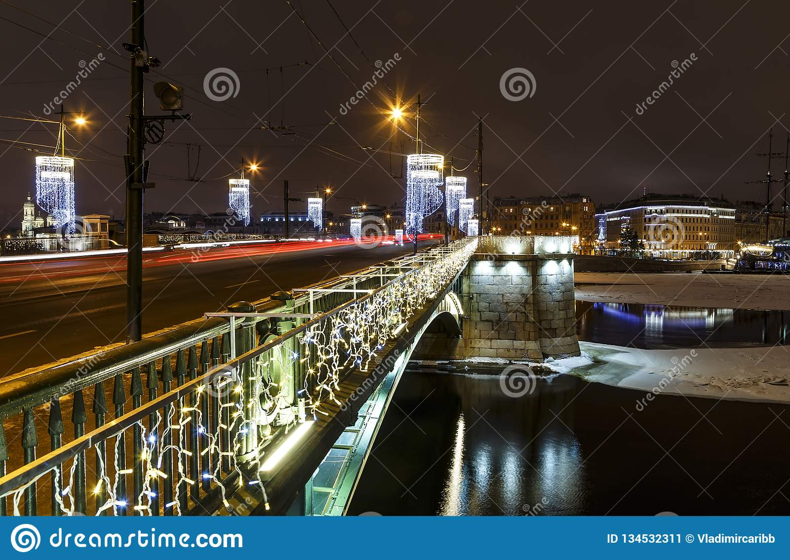 Neon blue illumination of the bridge across Neva river with water and reflection in it at night, cars and tracers from the