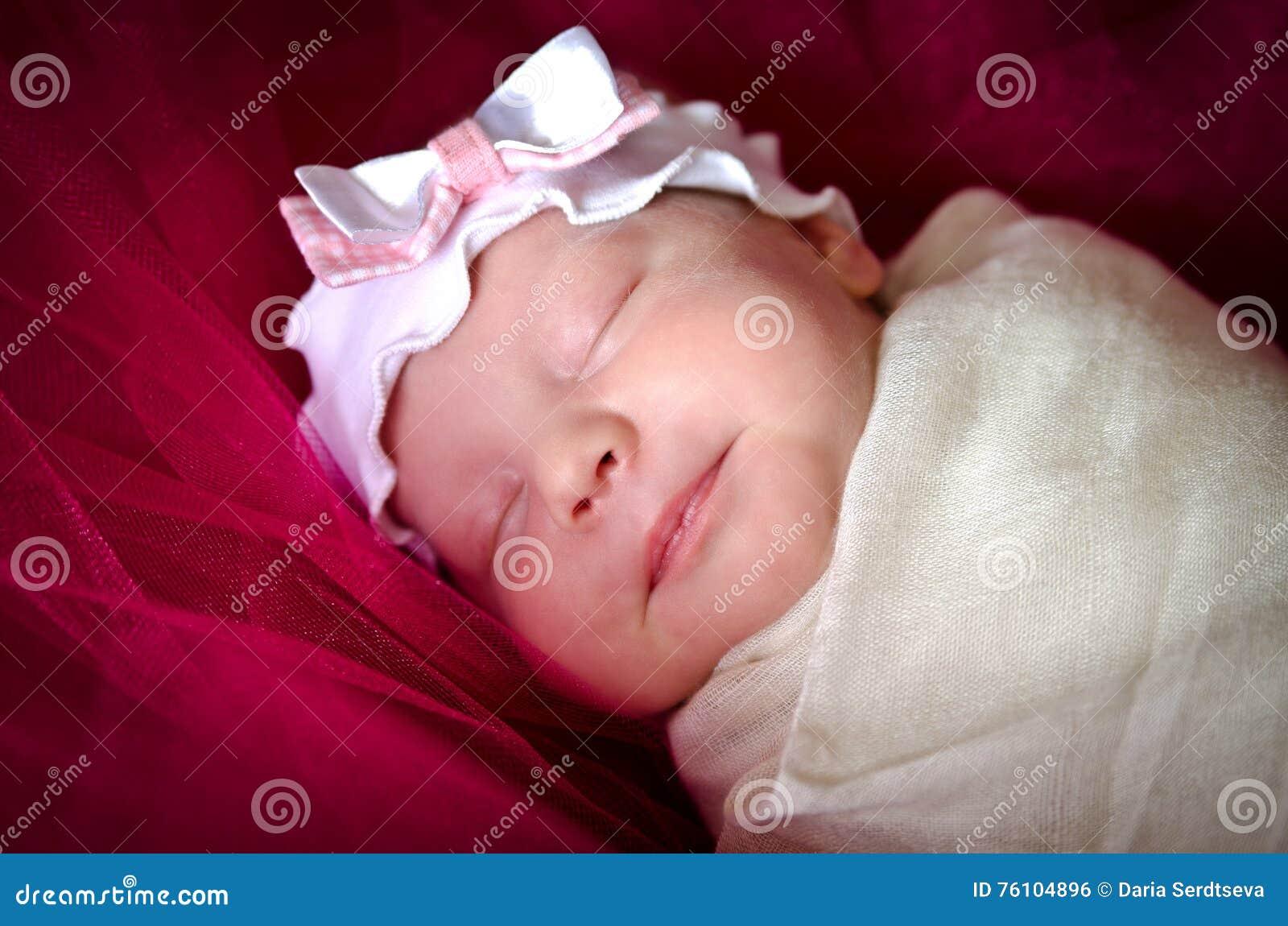 Neonata addormentata in un imbracatura sulla sua testa