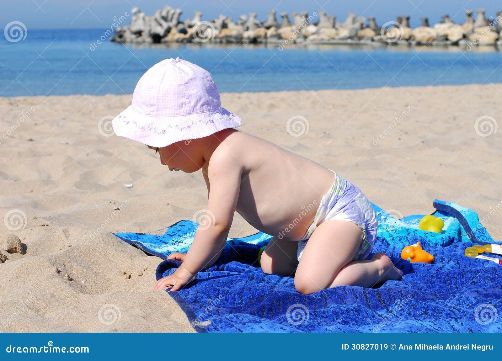 Neonata in buona salute che gioca sulla spiaggia