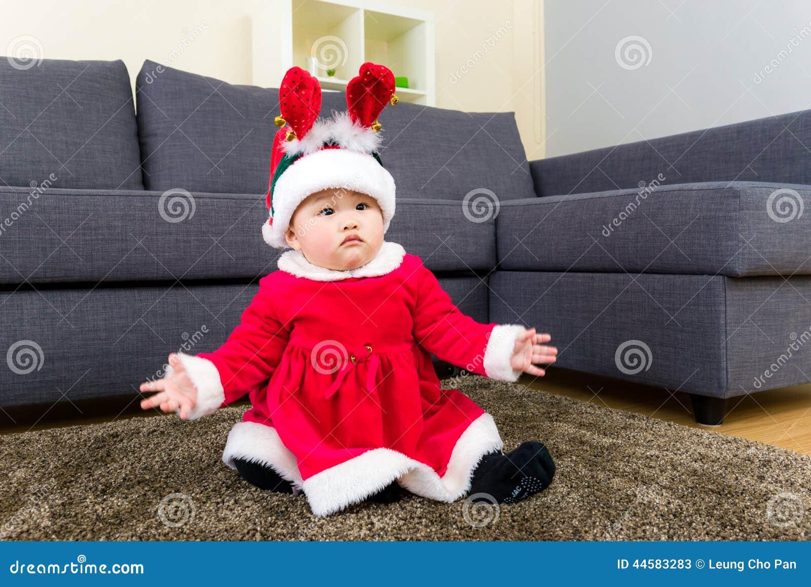 Neonata con mas di x che si veste e che si siede sul tappeto