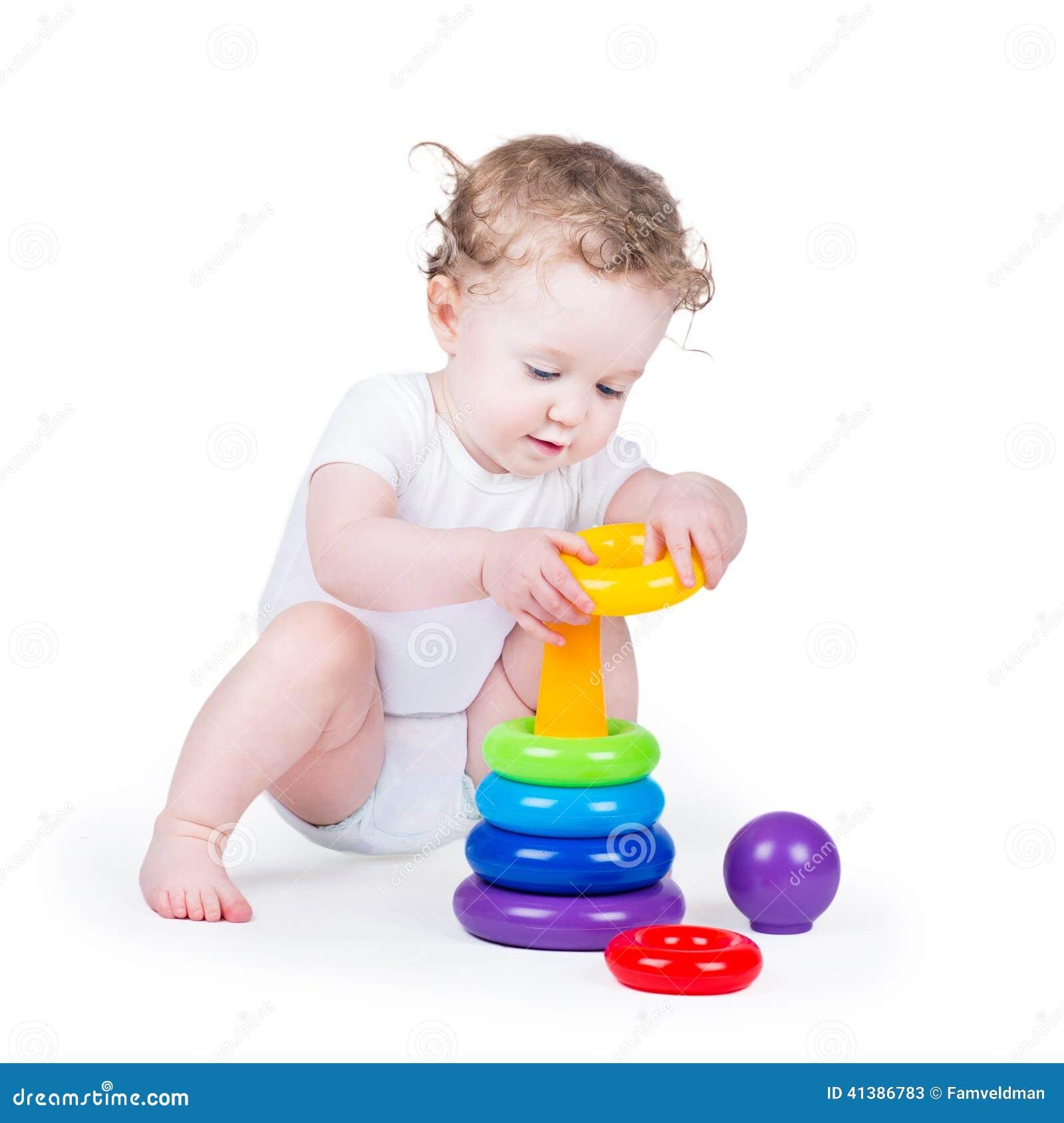 Neonata riccia divertente che gioca con una piramide variopinta
