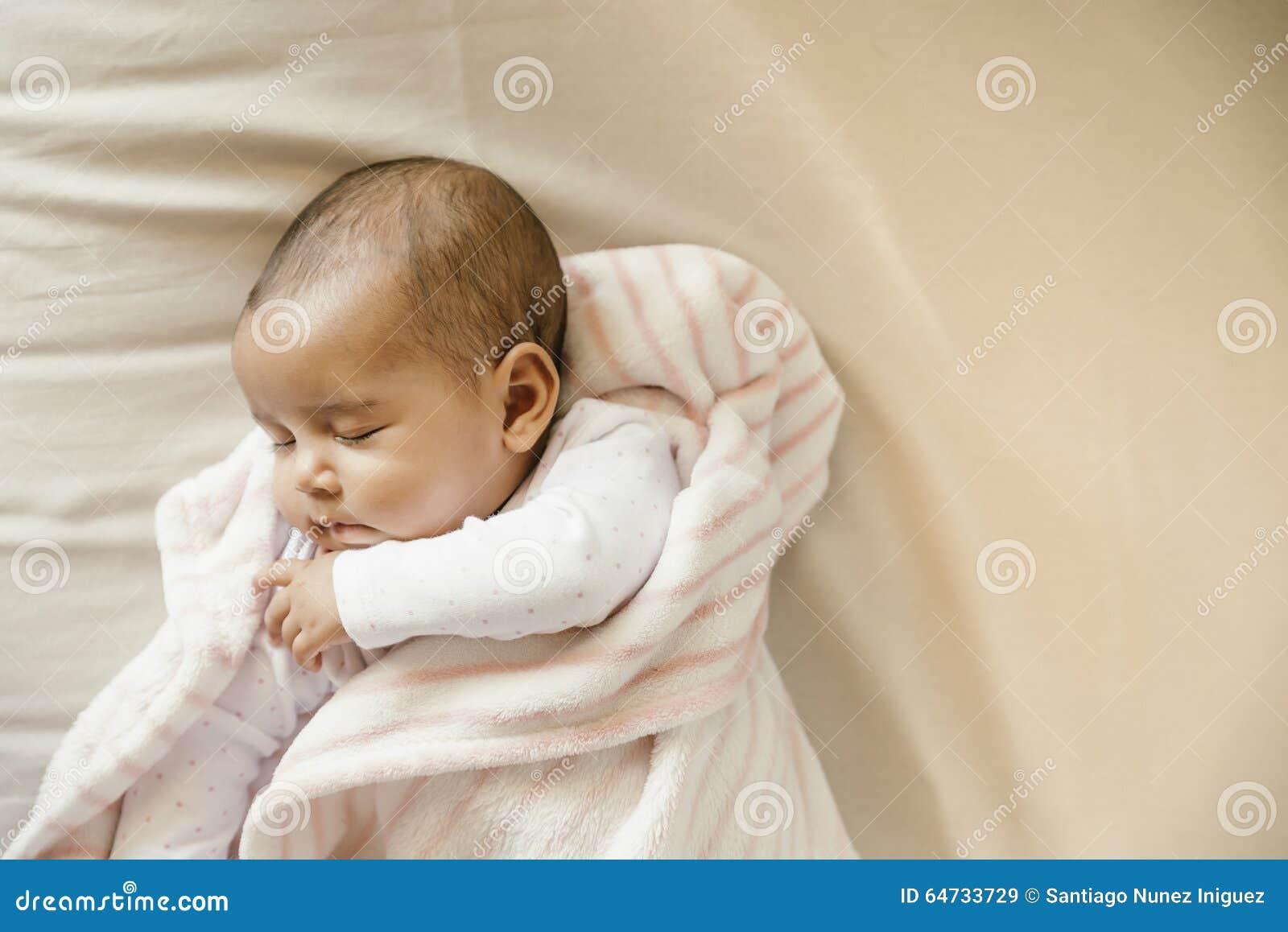 Neonata sveglia che dorme nella greppia