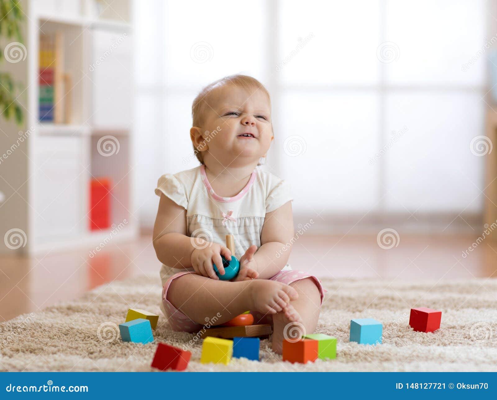 Neonata sveglia che gioca con i giocattoli in salone