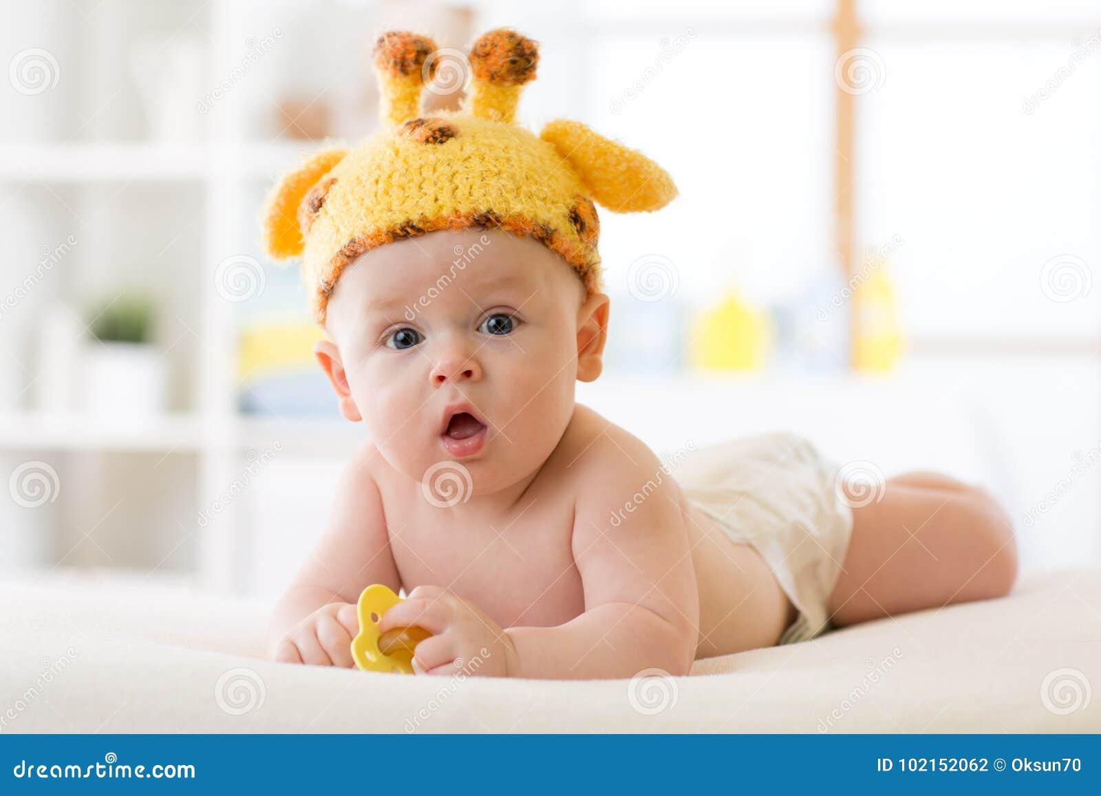 Neonato adorabile che si trova sulla pancia e sul cappello divertente weared della giraffa