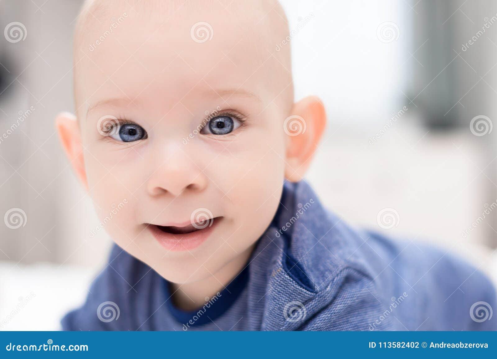 Neonato adorabile con gli occhi azzurri che esaminano direttamente la macchina fotografica che prova a raggiungere per  Fine sveg