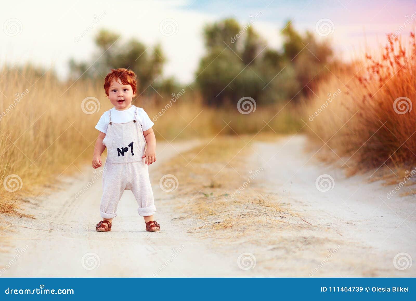 Neonato adorabile del bambino della testarossa in tuta che cammina lungo la strada rurale di estate nel campo scolorito al sole