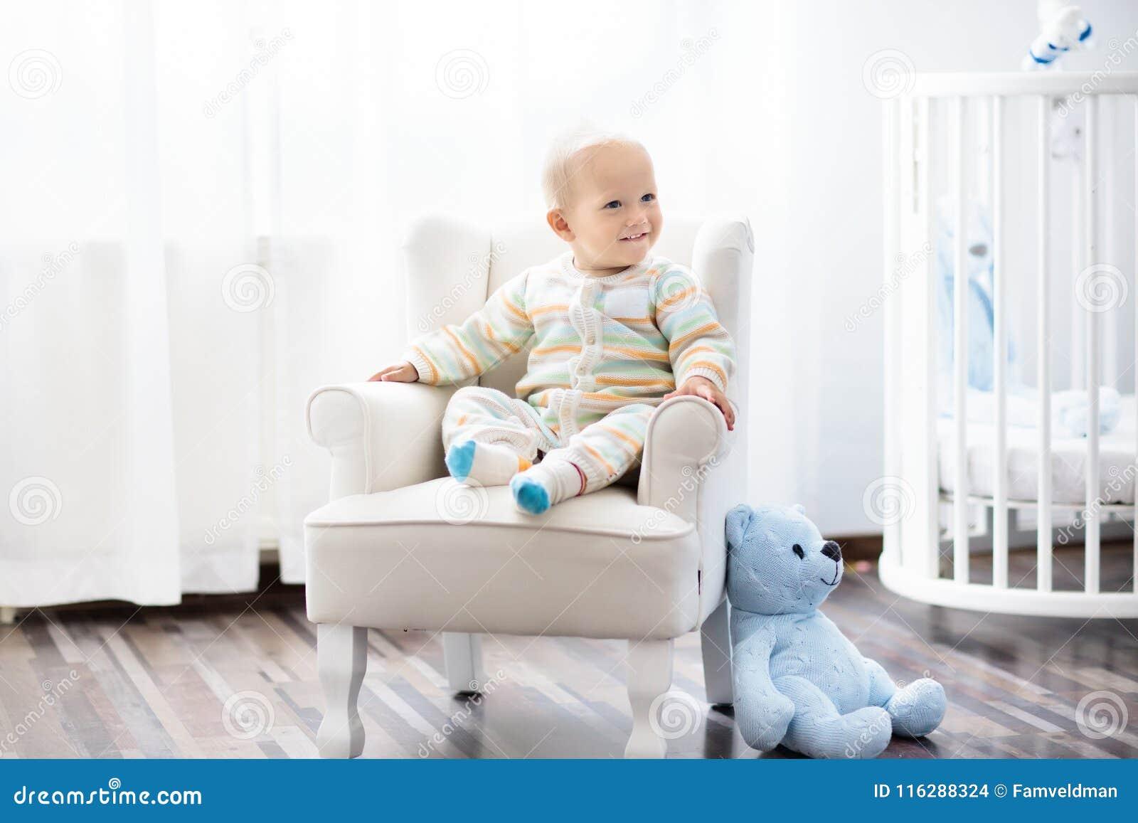 d01adae9cc Neonato in camera da letto Bambino infantile che si siede nella sedia  bianca al letto di legno rotondo Scherza l'interno della stanza I bambini  adattano e ...
