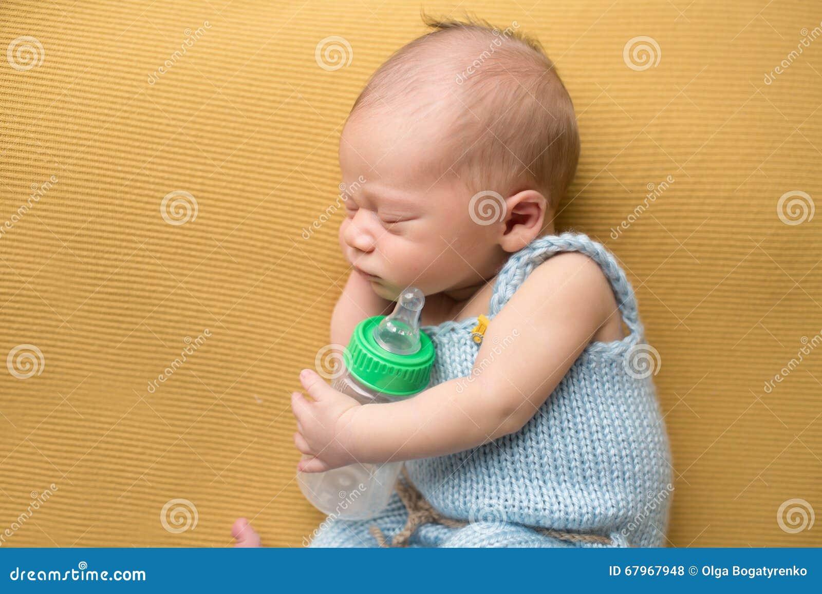 Neonato che dorme con la bottiglia