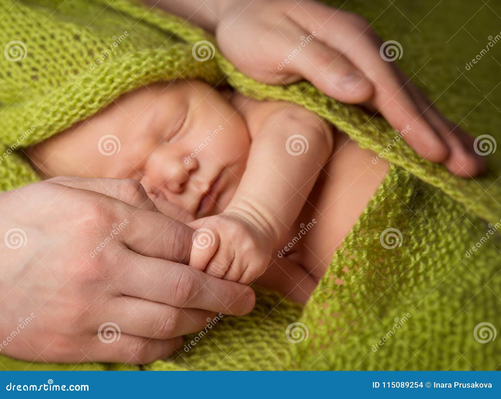 Neonato che dorme nel padre Hands, genitore che protegge nuovo Bor