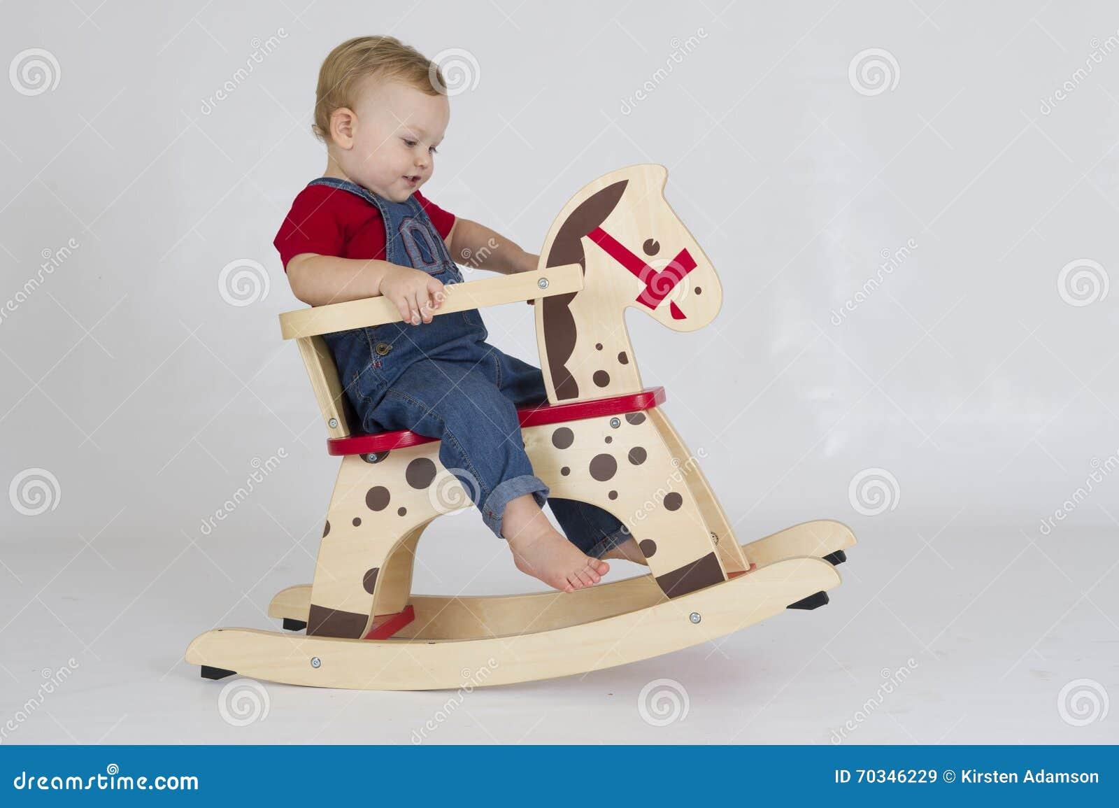 Cavallo A Dondolo In Legno.Neonato Che Monta Un Cavallo A Dondolo Di Legno Immagine Stock
