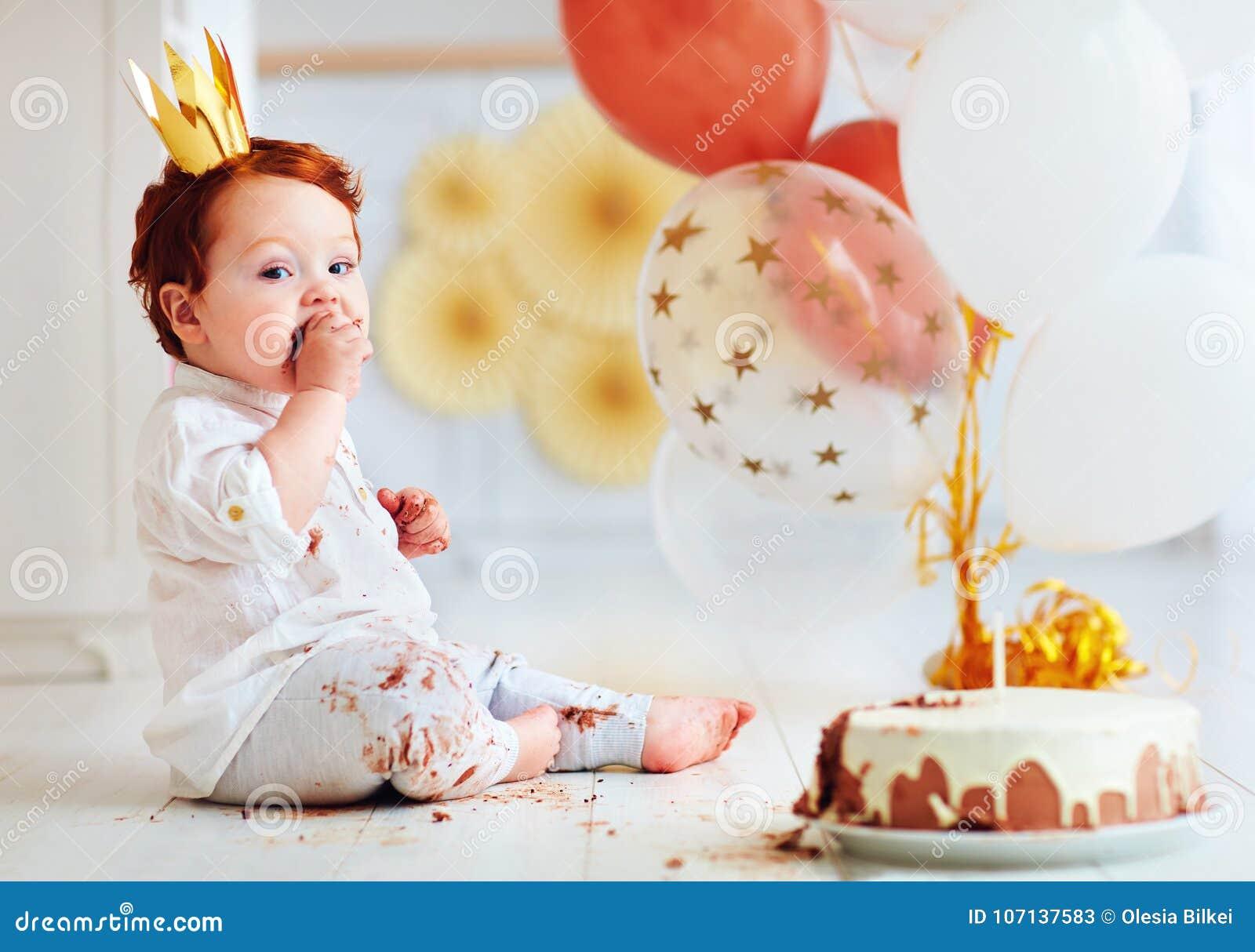 Neonato infantile divertente che assaggia la sua prima torta di compleanno