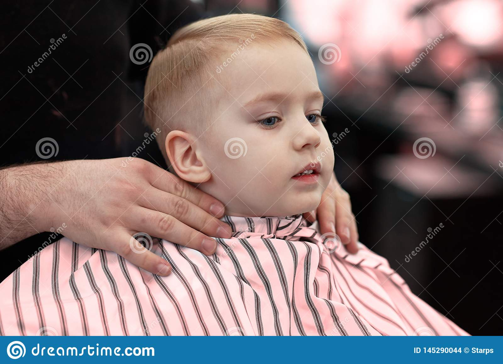 Neonato sorridente biondo sveglio con gli occhi azzurri in un negozio di barbiere che ha taglio di capelli dal parrucchiere Mani