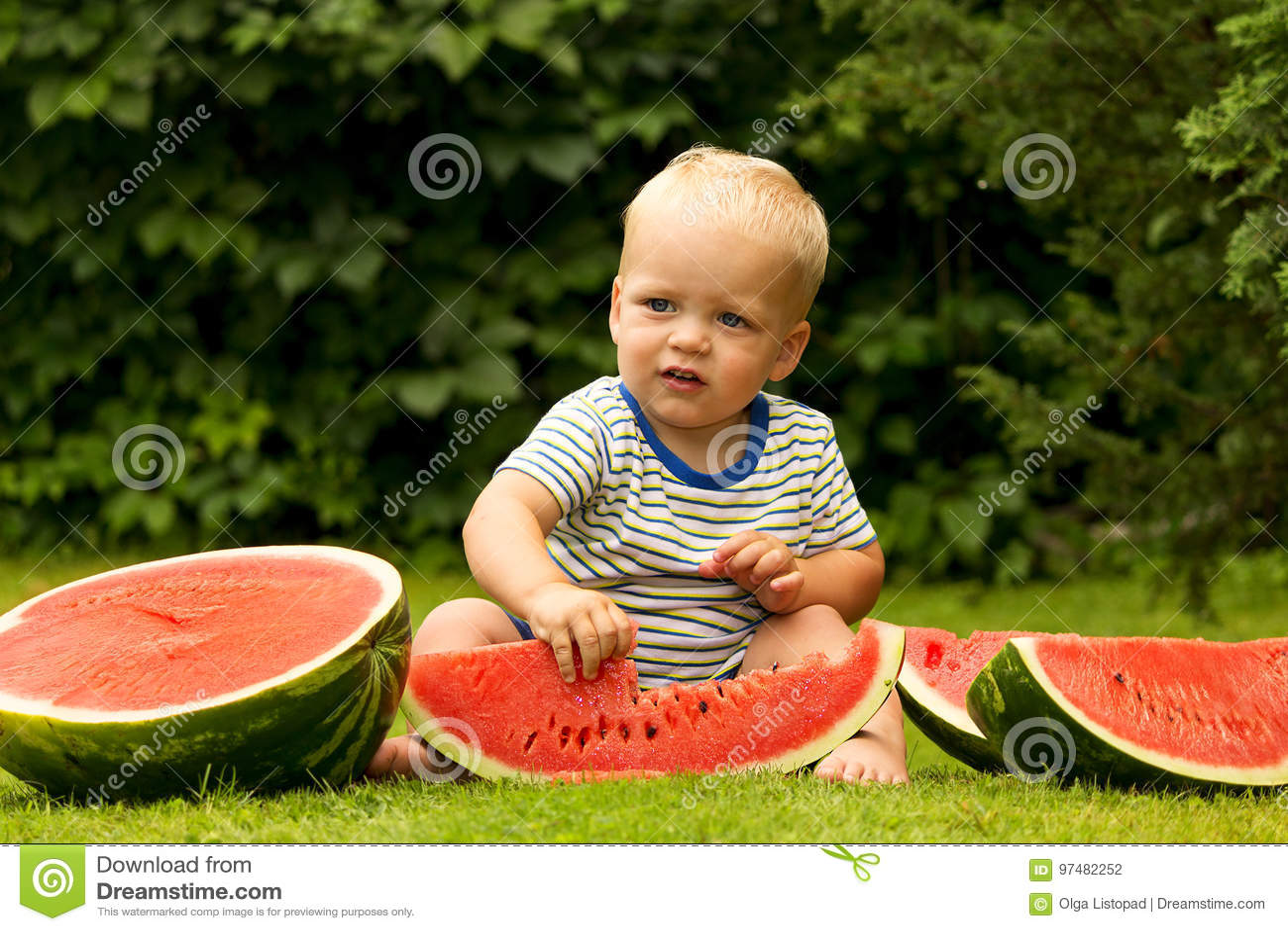 Neonato sveglio che mangia anguria sul prato inglese nel parco verde