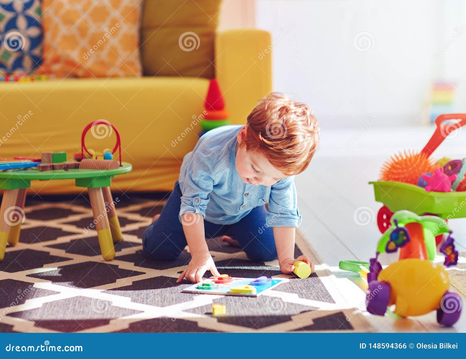 Neonato sveglio del bambino che gioca con i giocattoli sul tappeto a casa