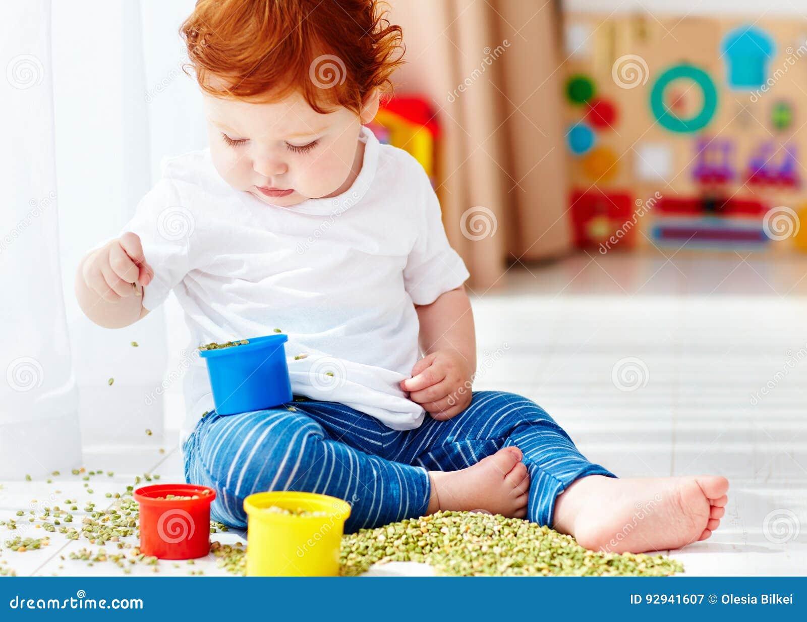Neonato sveglio della testarossa che sviluppa le sue abilità fini di motilità giocando con i piselli a casa