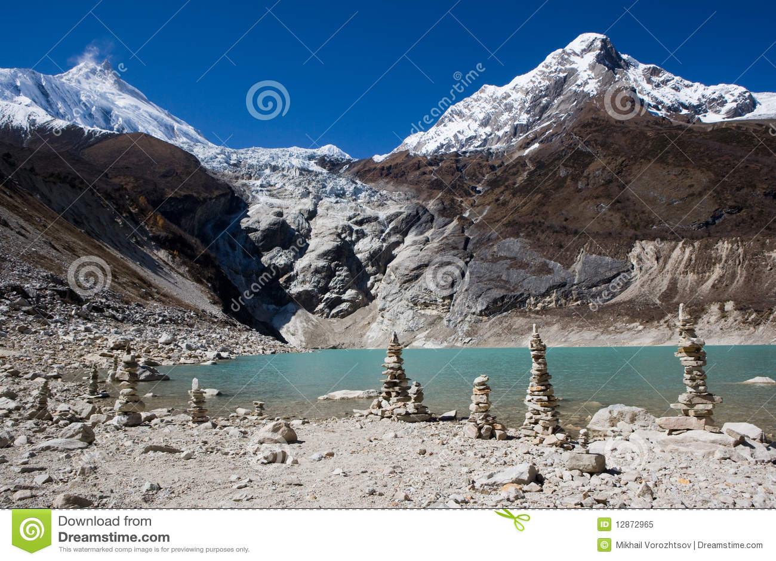 Nepal. Ijzig meer bij de bodem van bergManaslu