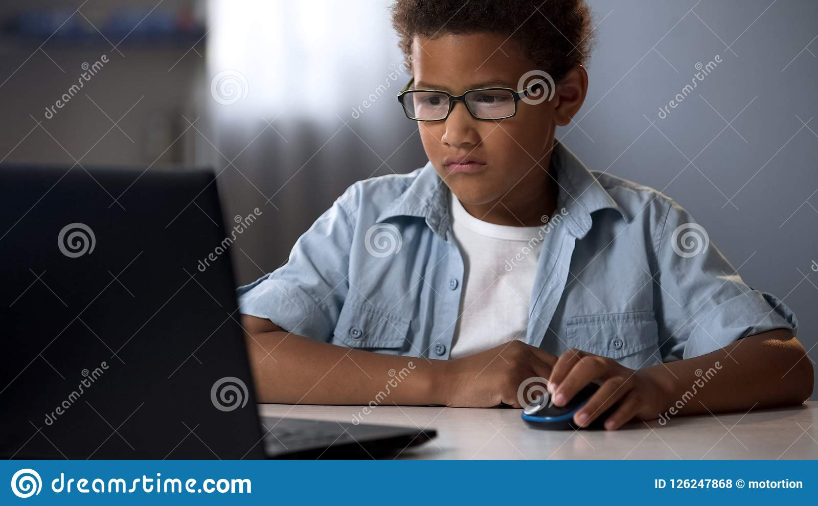 Nerd afroamericano che gioca i giochi di computer invece di apprendimento, dipendenza del bambino