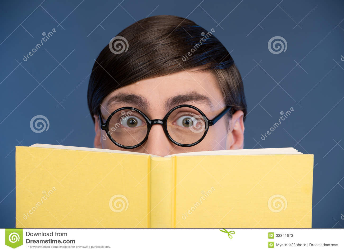 Young nerd man looking out of the book while isolated on blue.