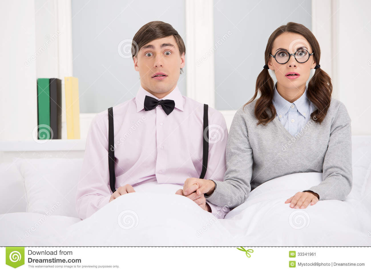 Nerd couple. Surprised nerd couple sitting on the bed and looking at camera