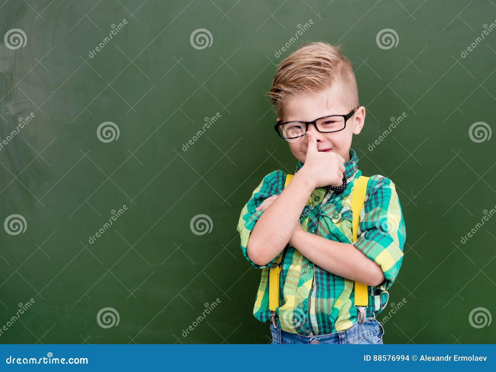 Nerd felice divertente vicino alla lavagna verde vuota