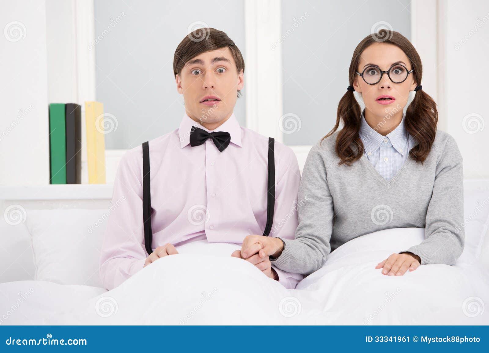 Nerdpaar. Verraste nerd paarzitting op het bed en lookin