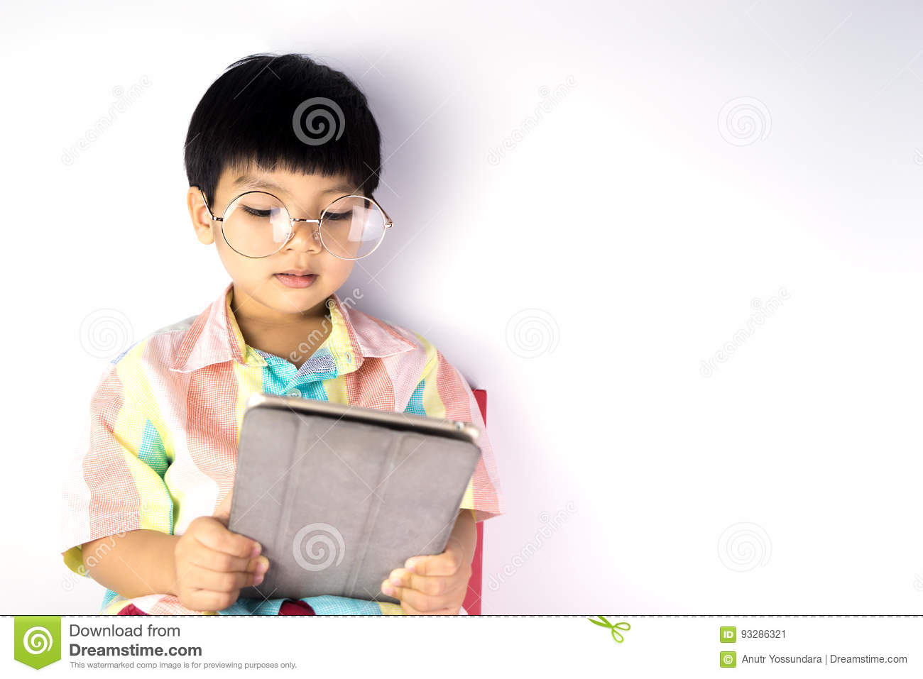 Nerdy Asian boy is reading on tablet