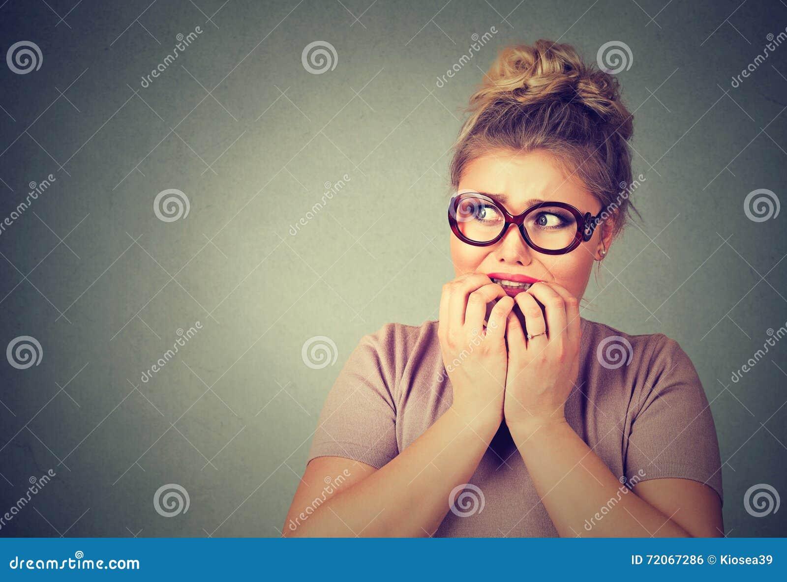 Nervöse betonte junge nerdy Frau in den Gläsern die Fingernägel beißend, die besorgt schauen
