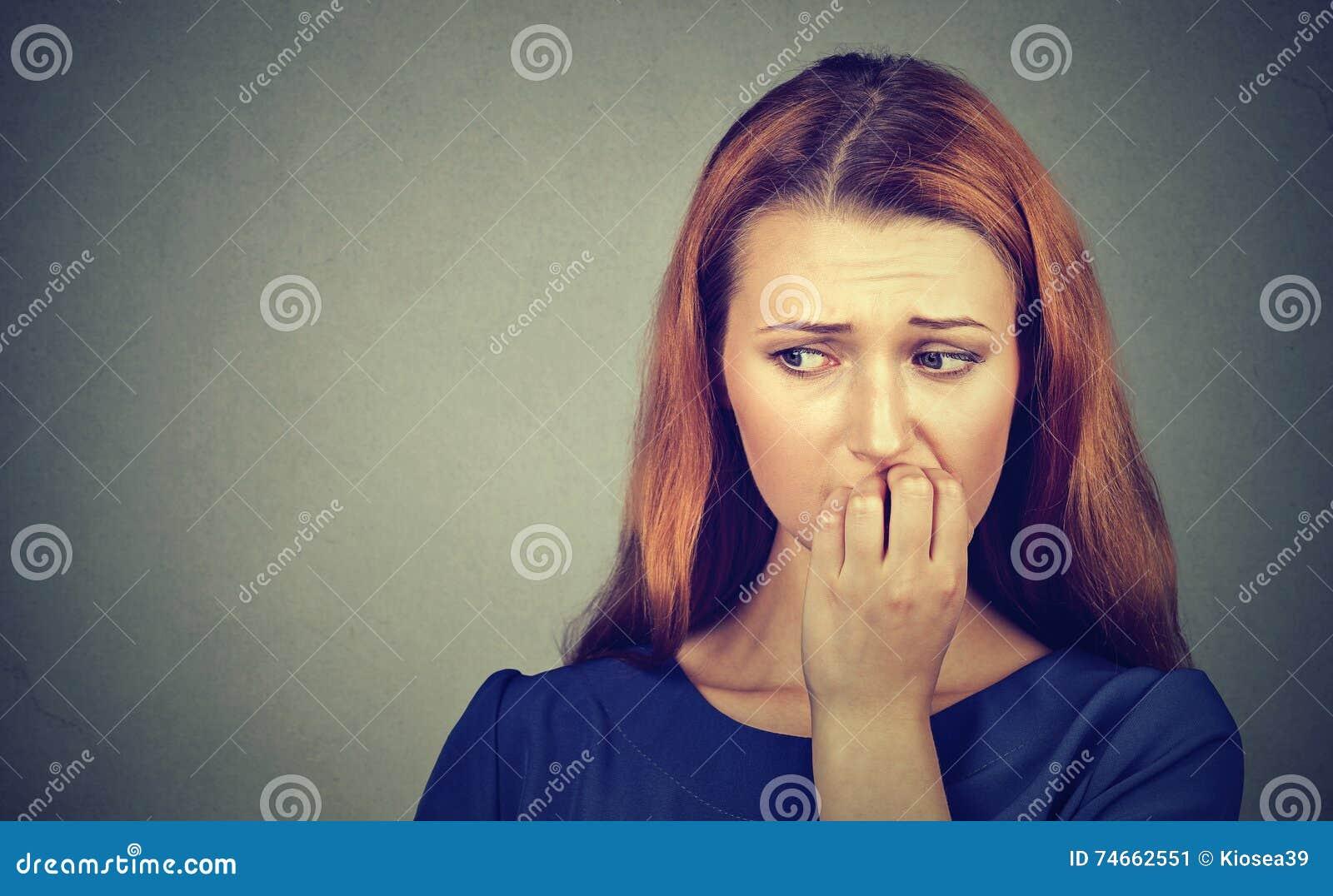 Nervöse Frau, die ihre Fingernägel sich sehnen etwas beißen oder besorgt
