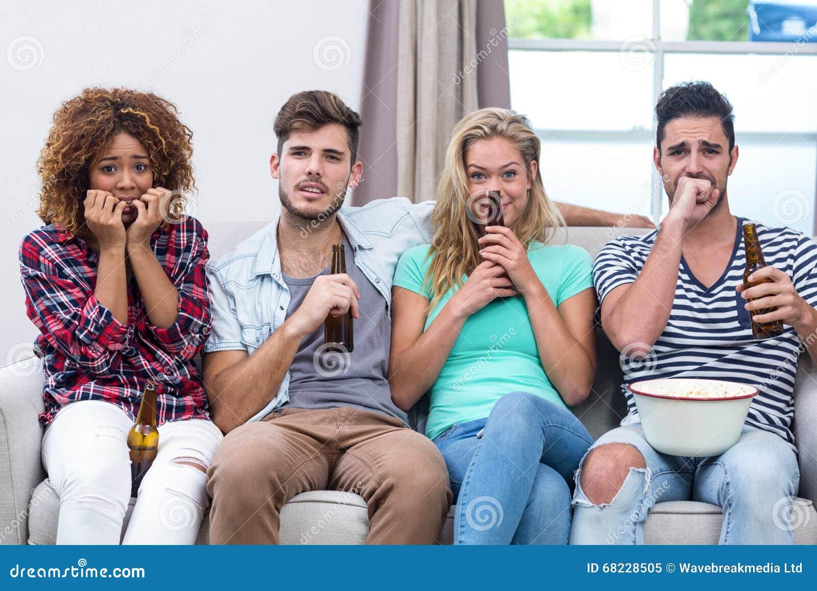 Nervöse multiethnische Freunde, die zu Hause fernsehen