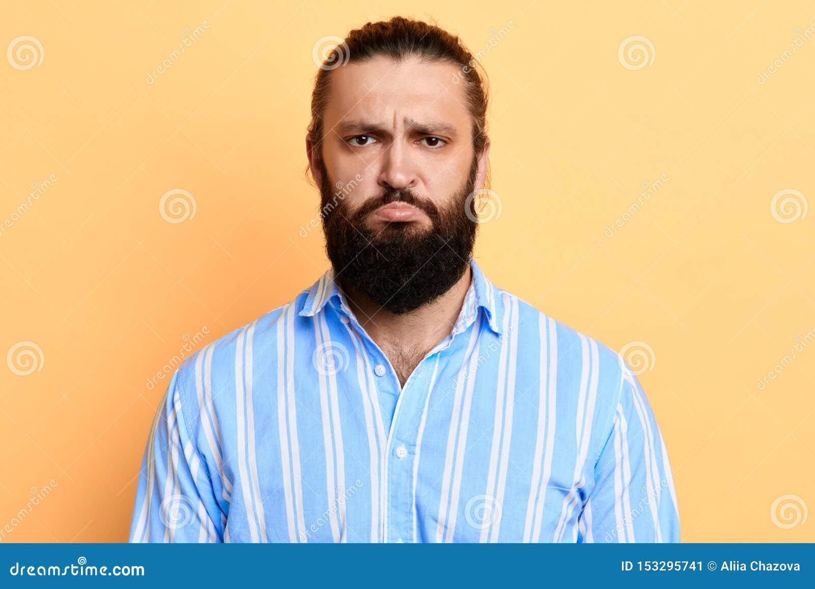 Nervöser zweifelhafter hübscher bärtiger die Stirn runzelnder Mann seine Augenbrauen