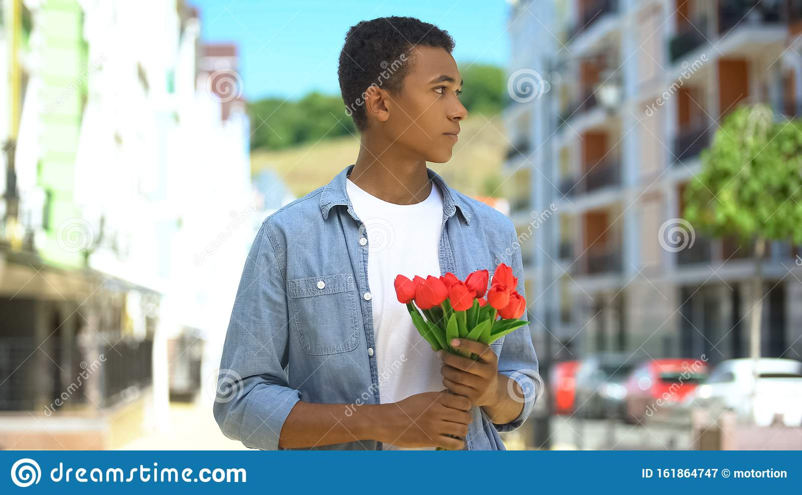 Nervous Young Male With Tulips Bouquet Waiting For Girl On