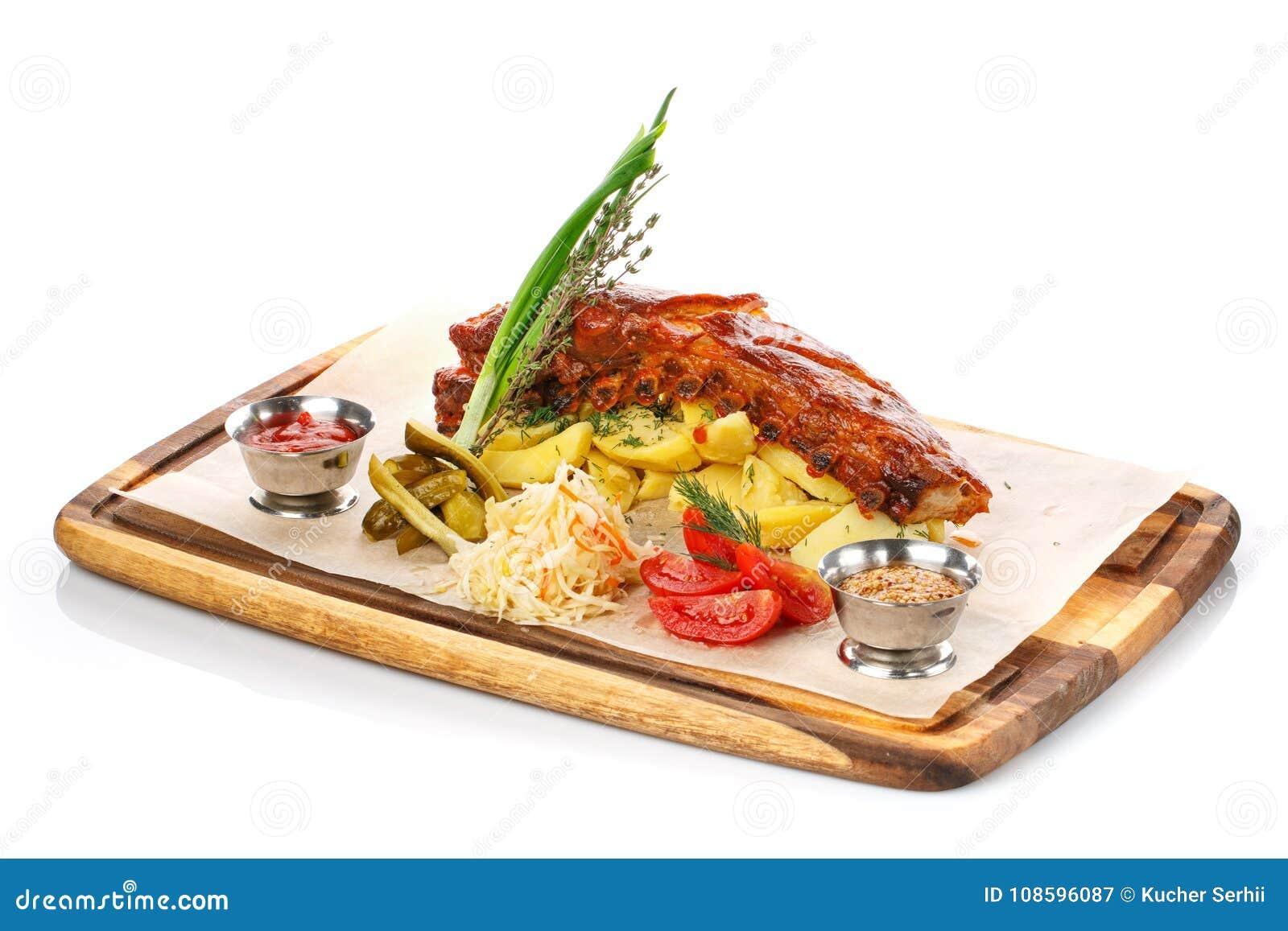 Nervure et Fried Potato de porc grillés délicieux avec de la sauce et des légumes sur la planche à découper en bois,