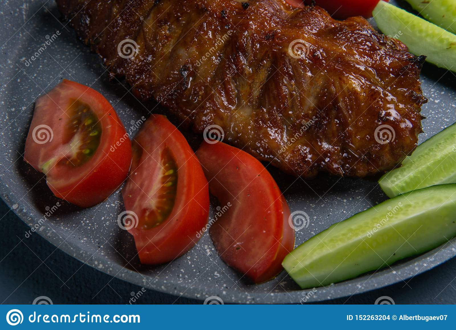 Nervures de porc cuites au four avec le mensonge de miel avec les tomates et les concombres coupés en tranches frais de ‹d †de