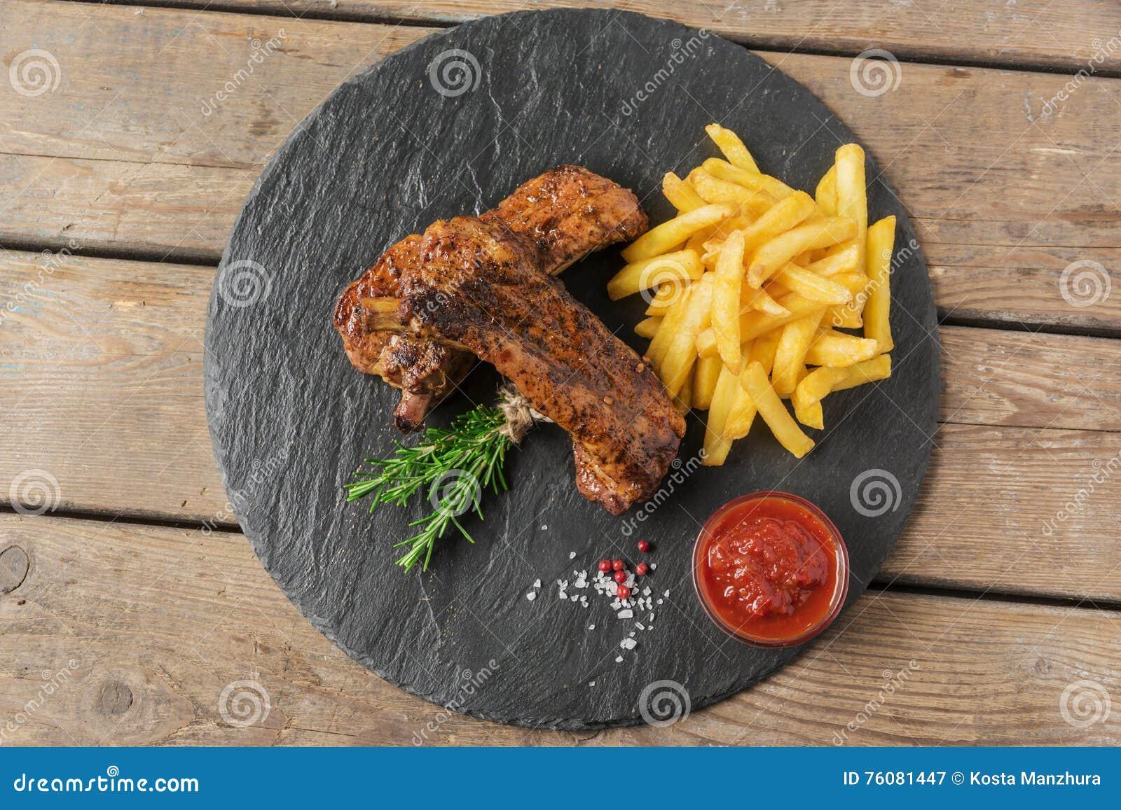 Nervures de porc cuites au four avec les pommes frites et la sauce rouge