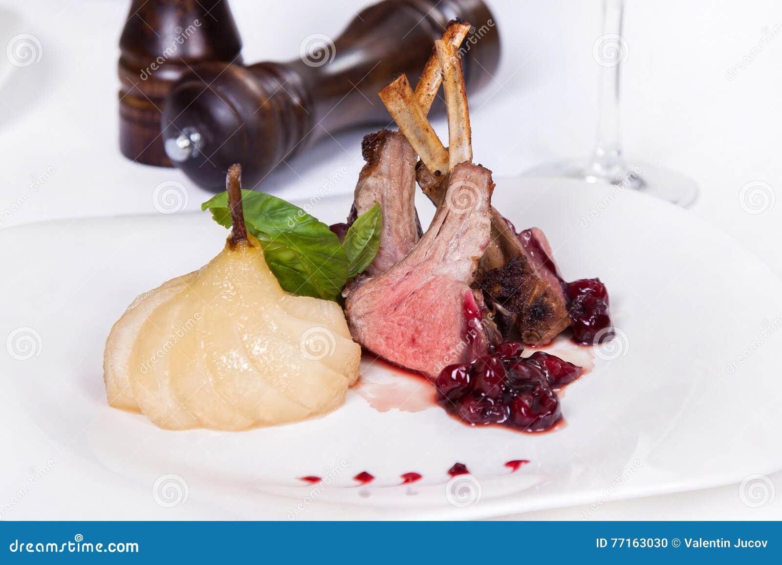 Nervures rôties d agneau avec de la sauce, le basilic et la poire Plat chaud de viande sur le fond blanc