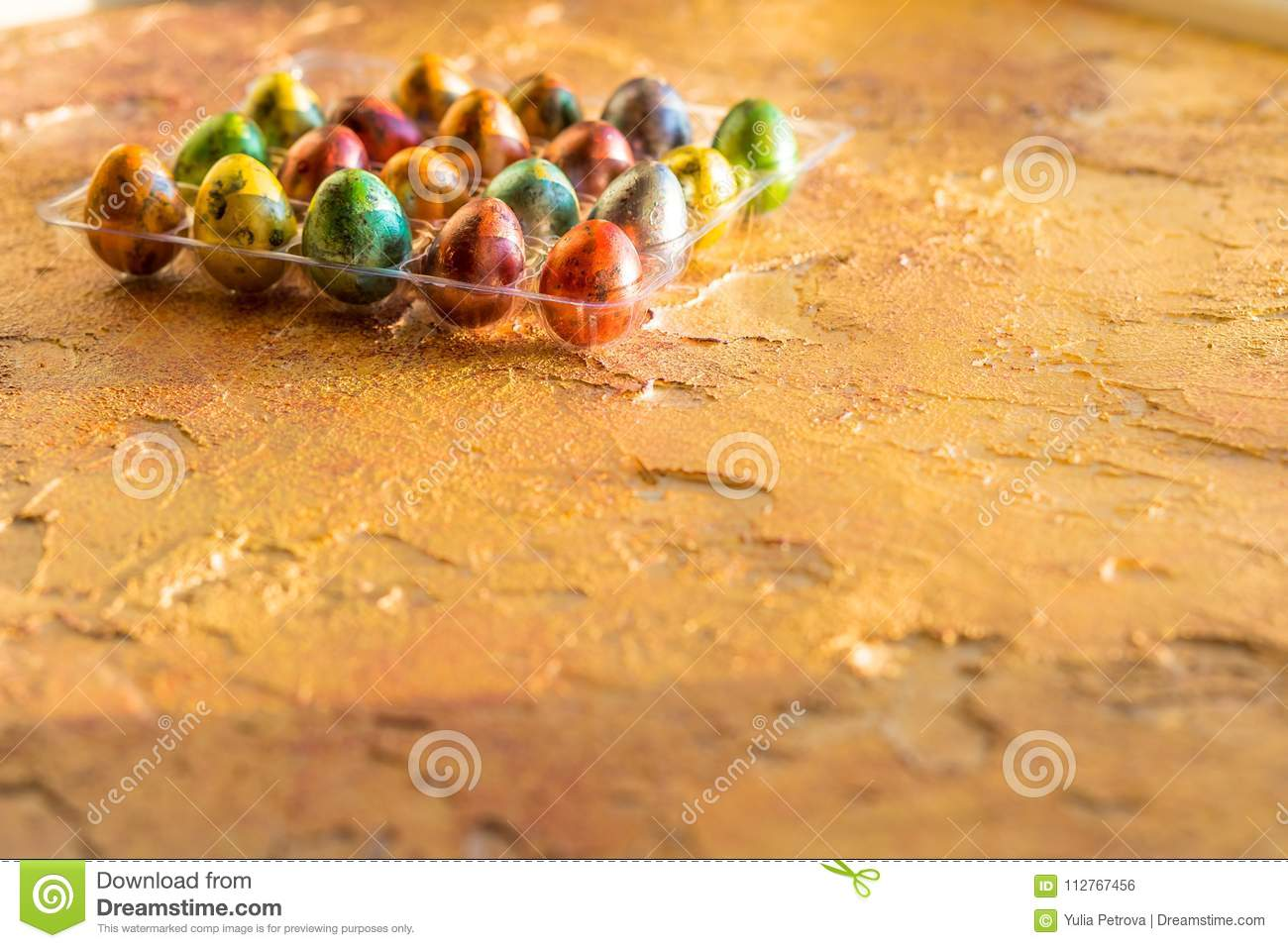 Quail egg in nest, spring, isolated on yellow.Corner of a tray of colorful eggs. Happy easter concept. Selective focus