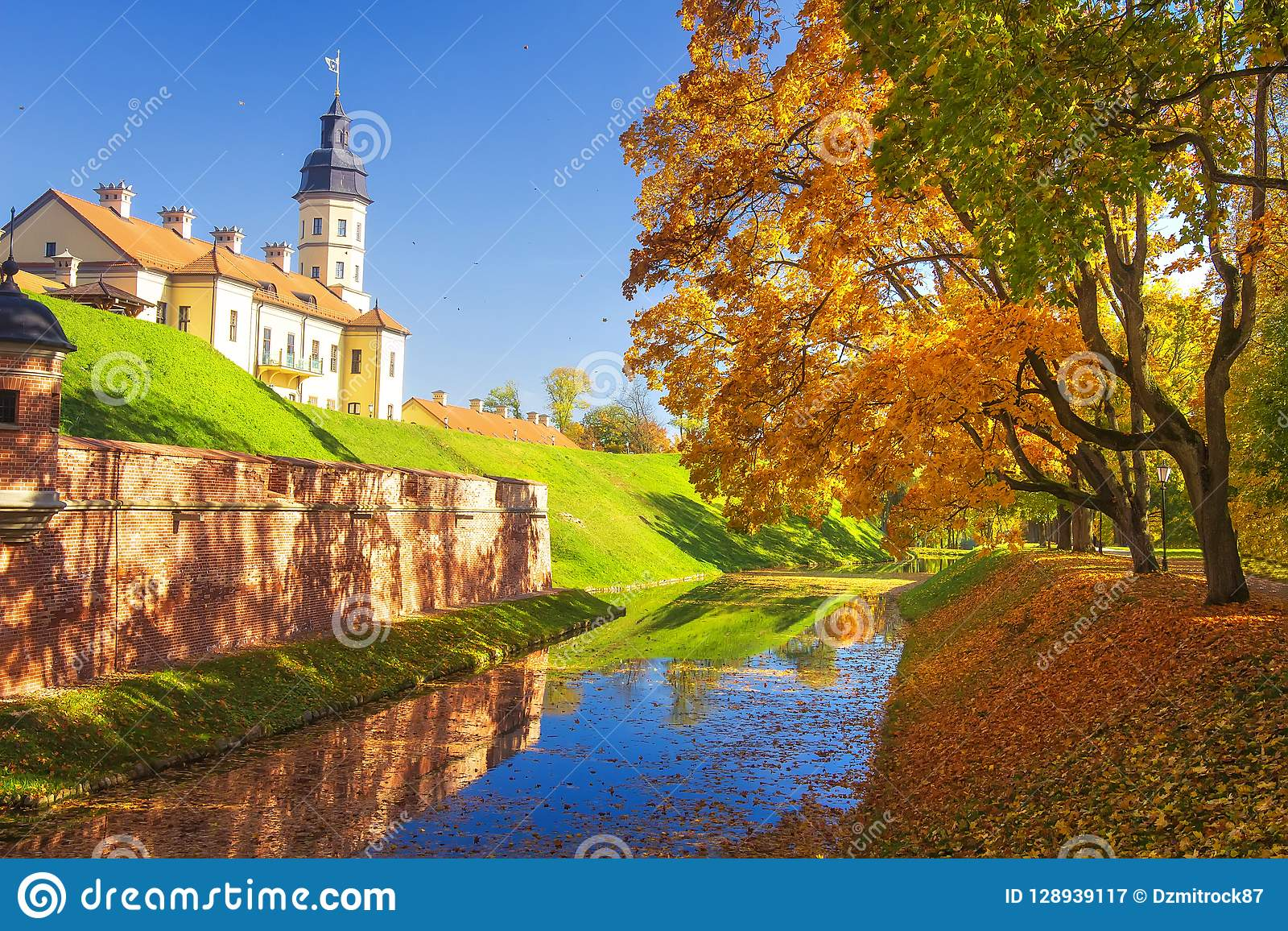 Nesvizh castle at autumn sunny clear day. Colourful yellow and red trees, blue sky, green grass, falling autumnal leaves