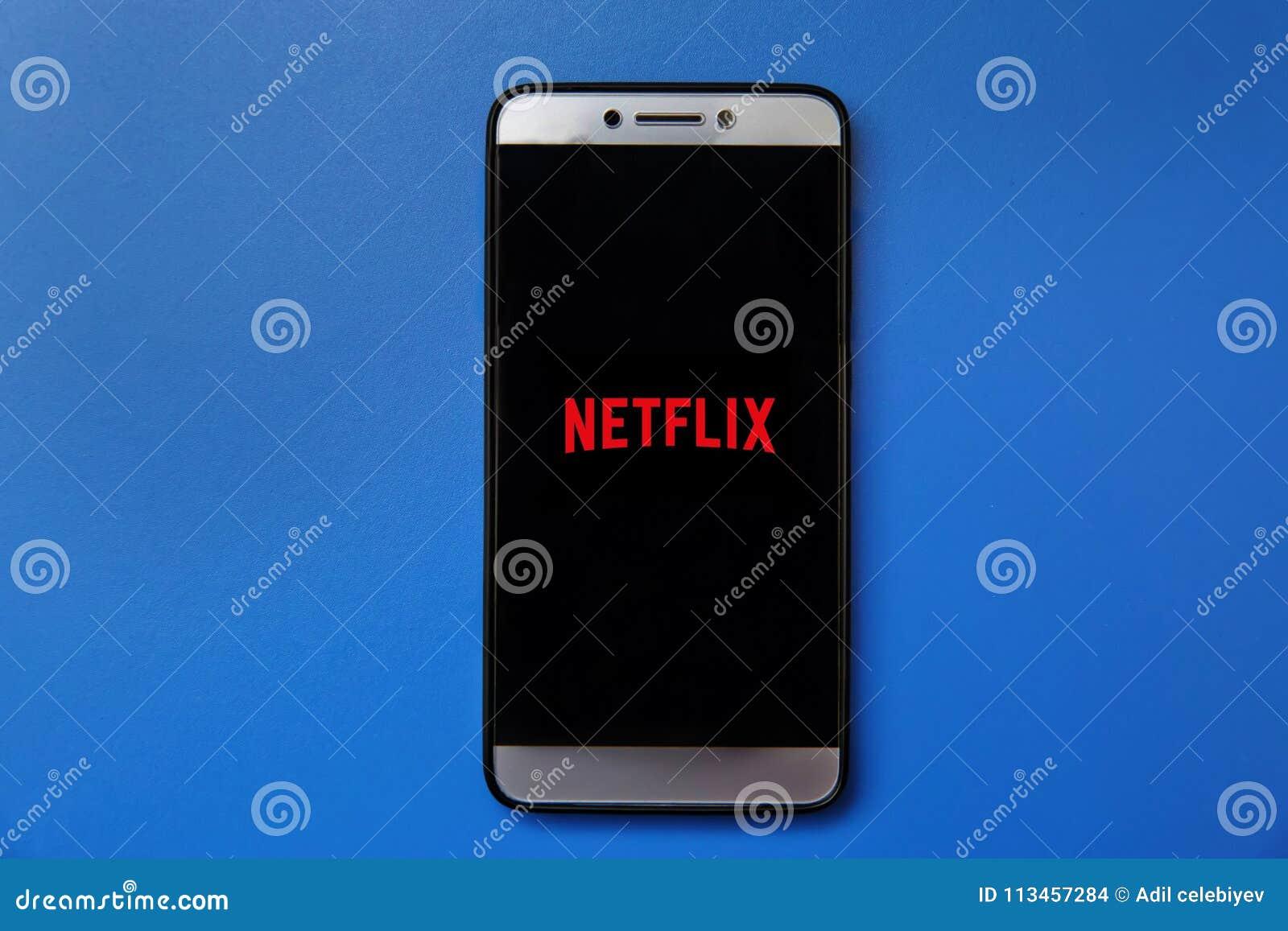 Netflix logo na smartphone ekranie na błękitnym tle Obsługuje mienia smartphone z Netflix logem na ekranie