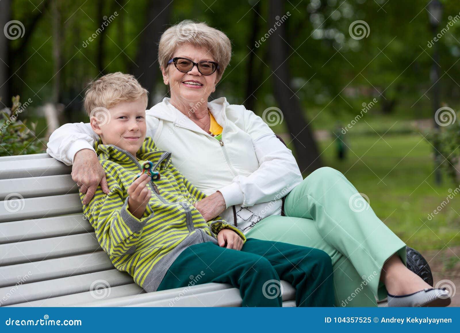 Neto de sorriso que joga com dispositivo do girador, avó feliz que abraça o menino, duas pessoas