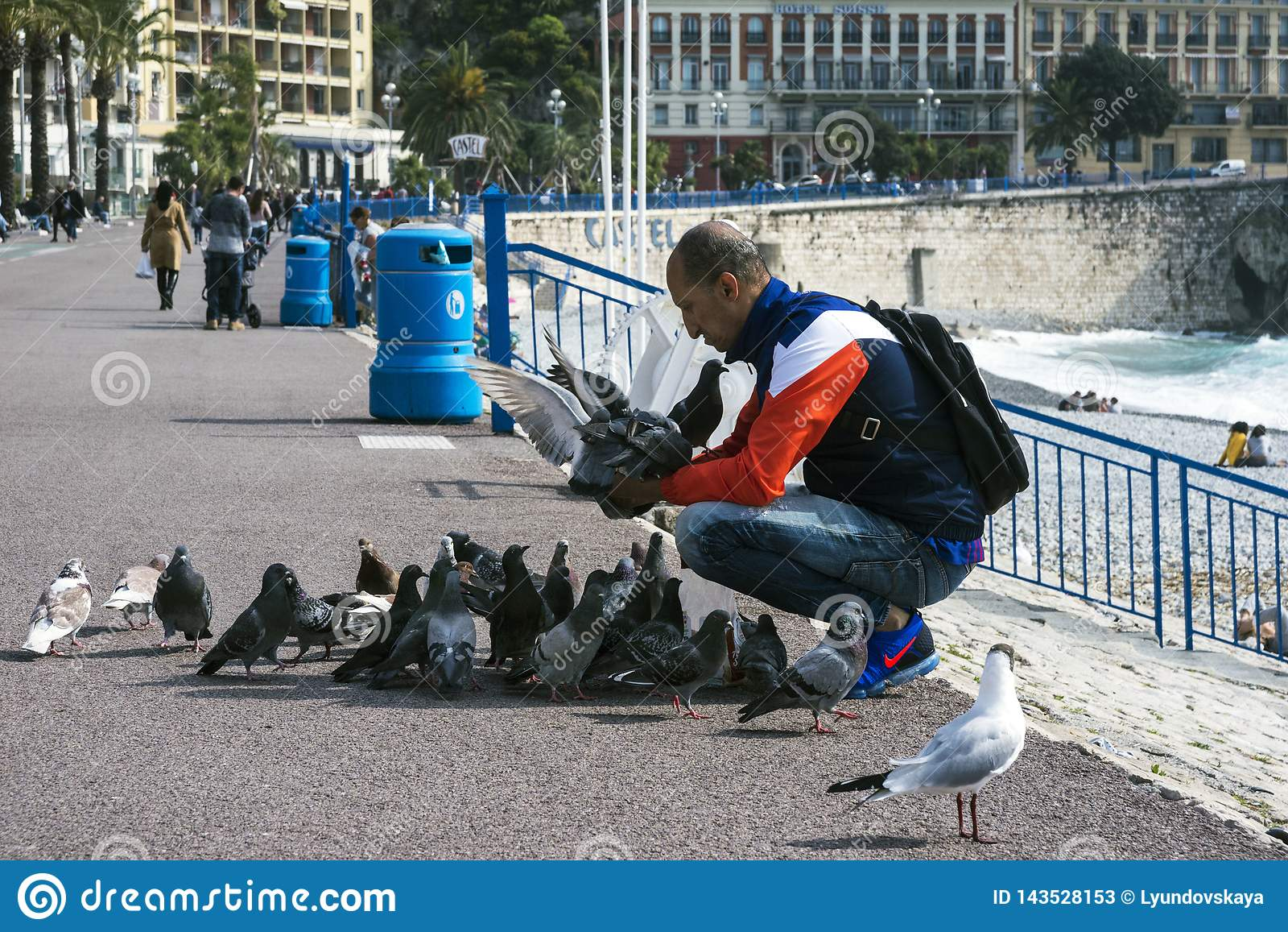 Nett, Frankreich, im März 2019 An einem warmen sonnigen Tag zieht ein Mann die Tauben der Stadt mit Brot gegen das Türkismeer von