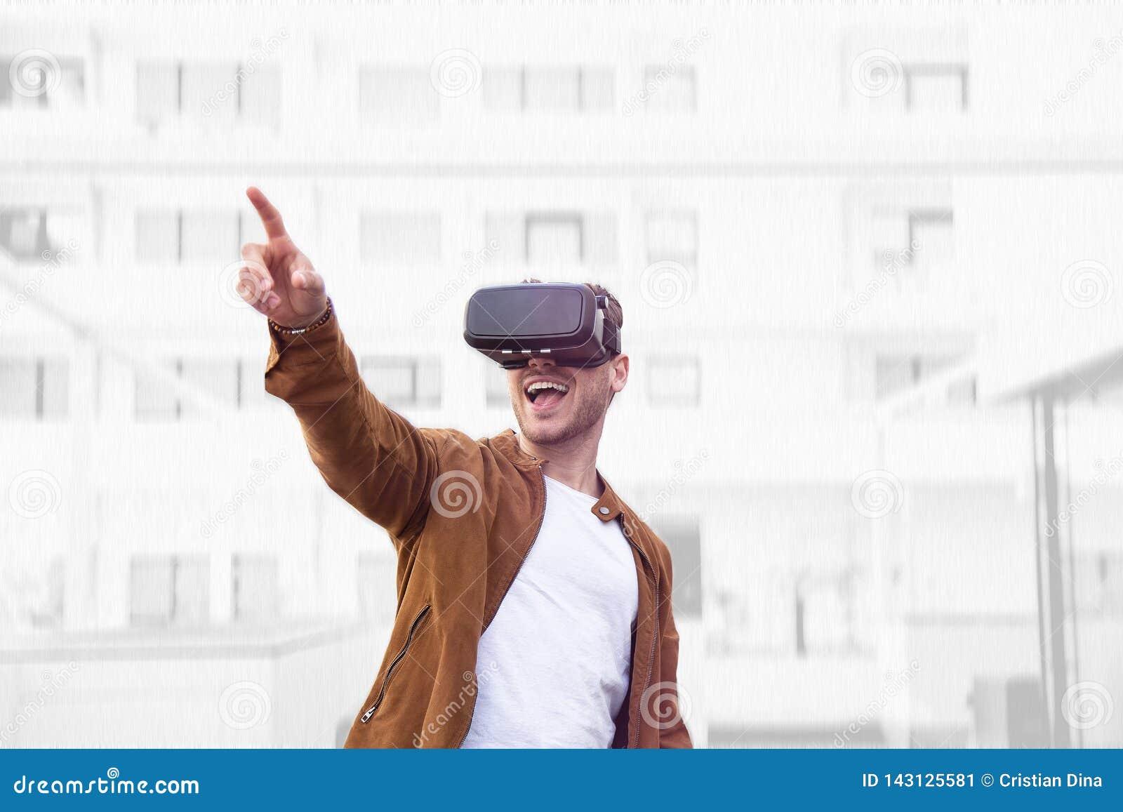 Nett junger erwachsener reizend Mann unter Verwendung der Gläser VR-virtueller Realität im Freien