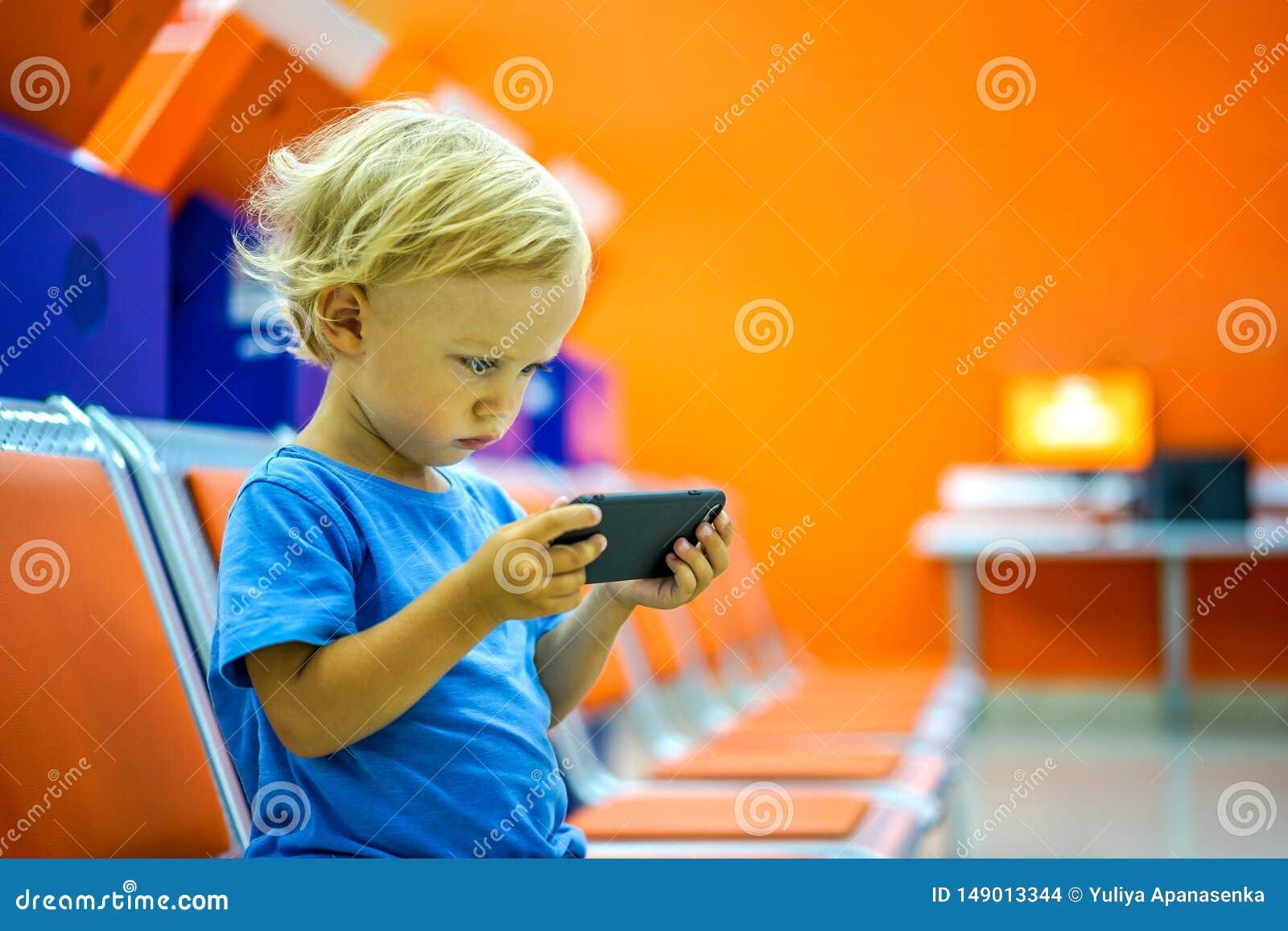 Nette aufpassende Karikaturen des kleinen Jungen auf Smartphone im Warteraum