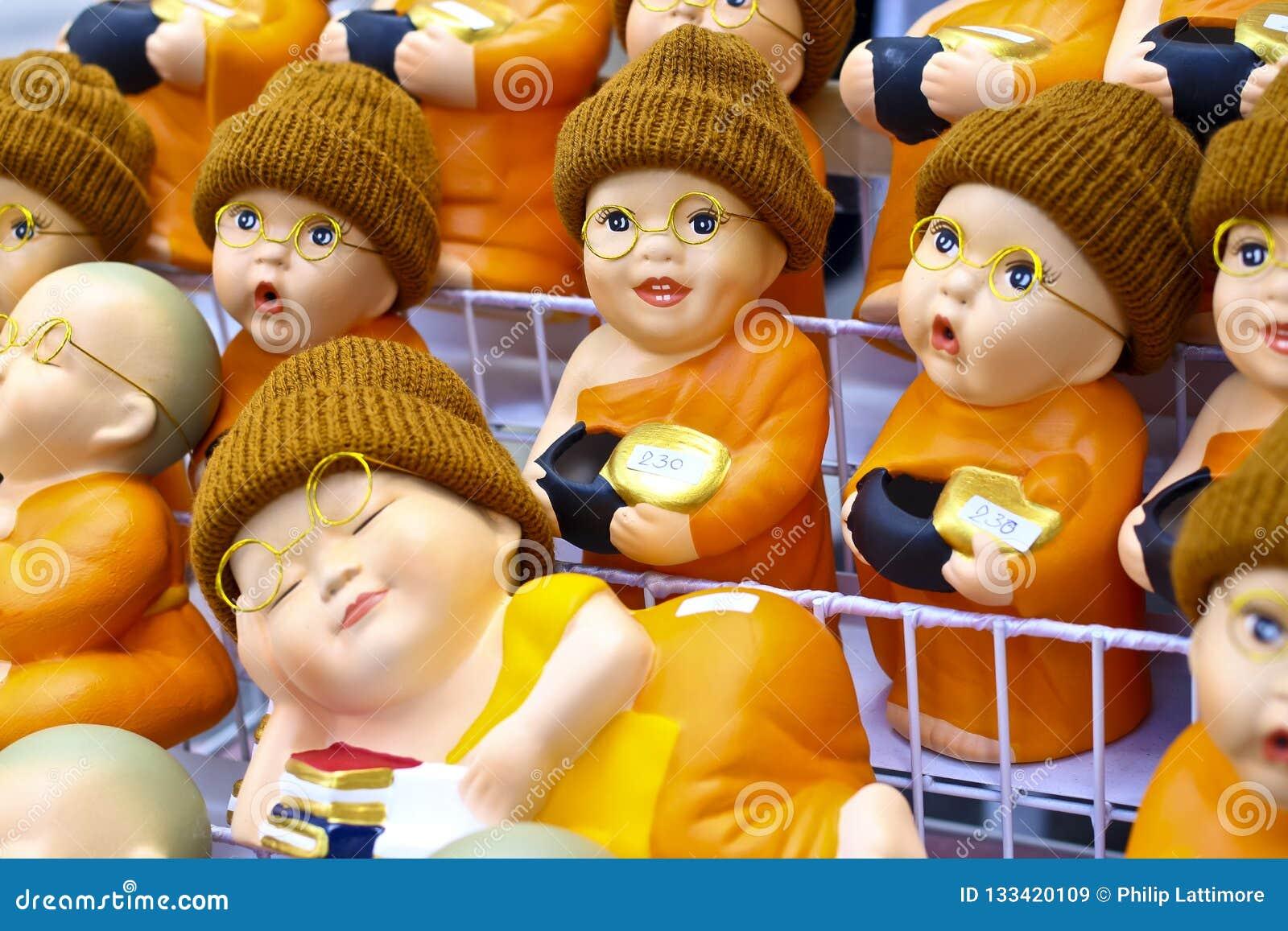 Nette Figürchen des buddhistischen Mönchs mit Schauspielen und wolligen Hüten