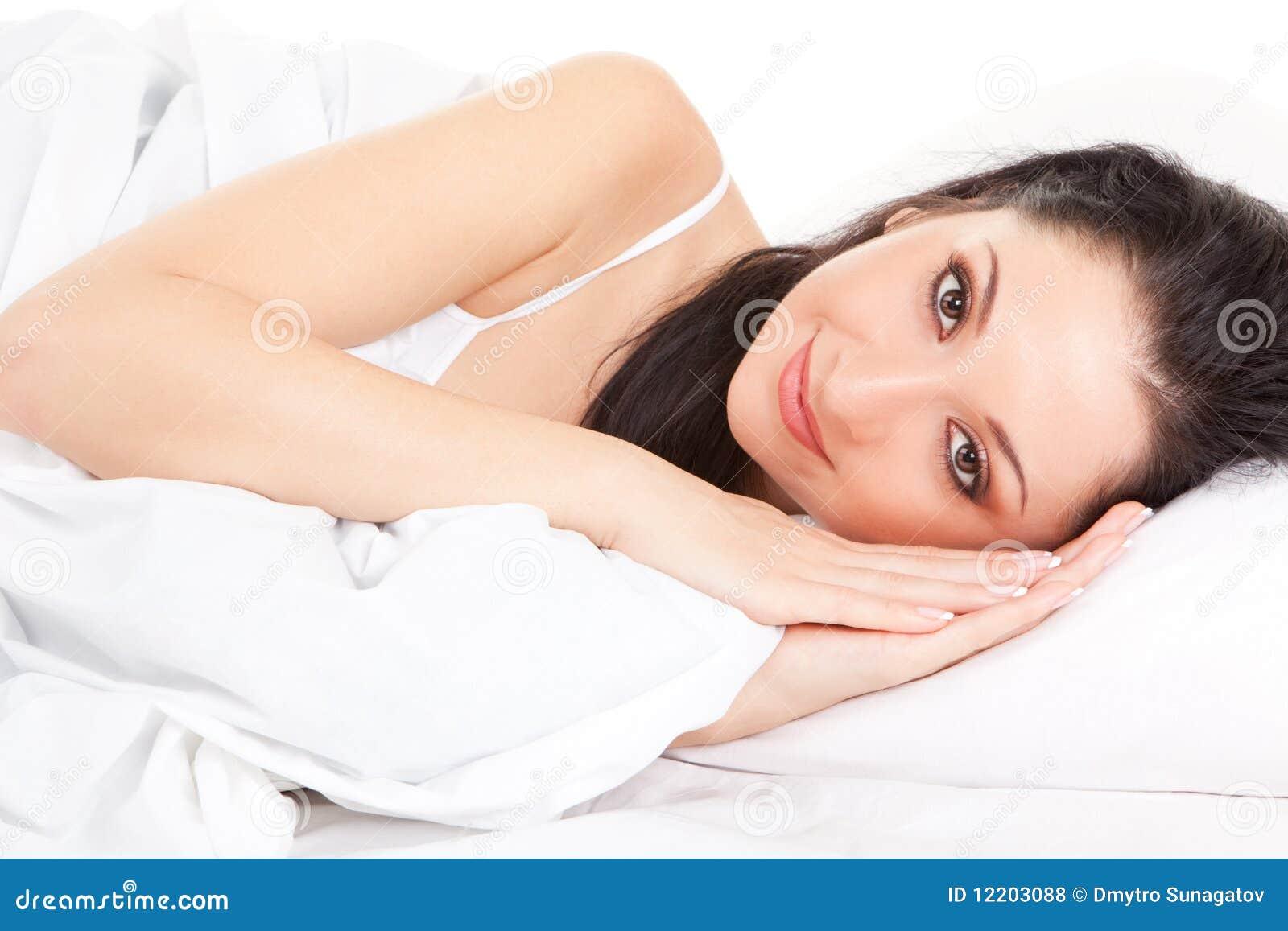 Nette Frau auf dem weißen Bett