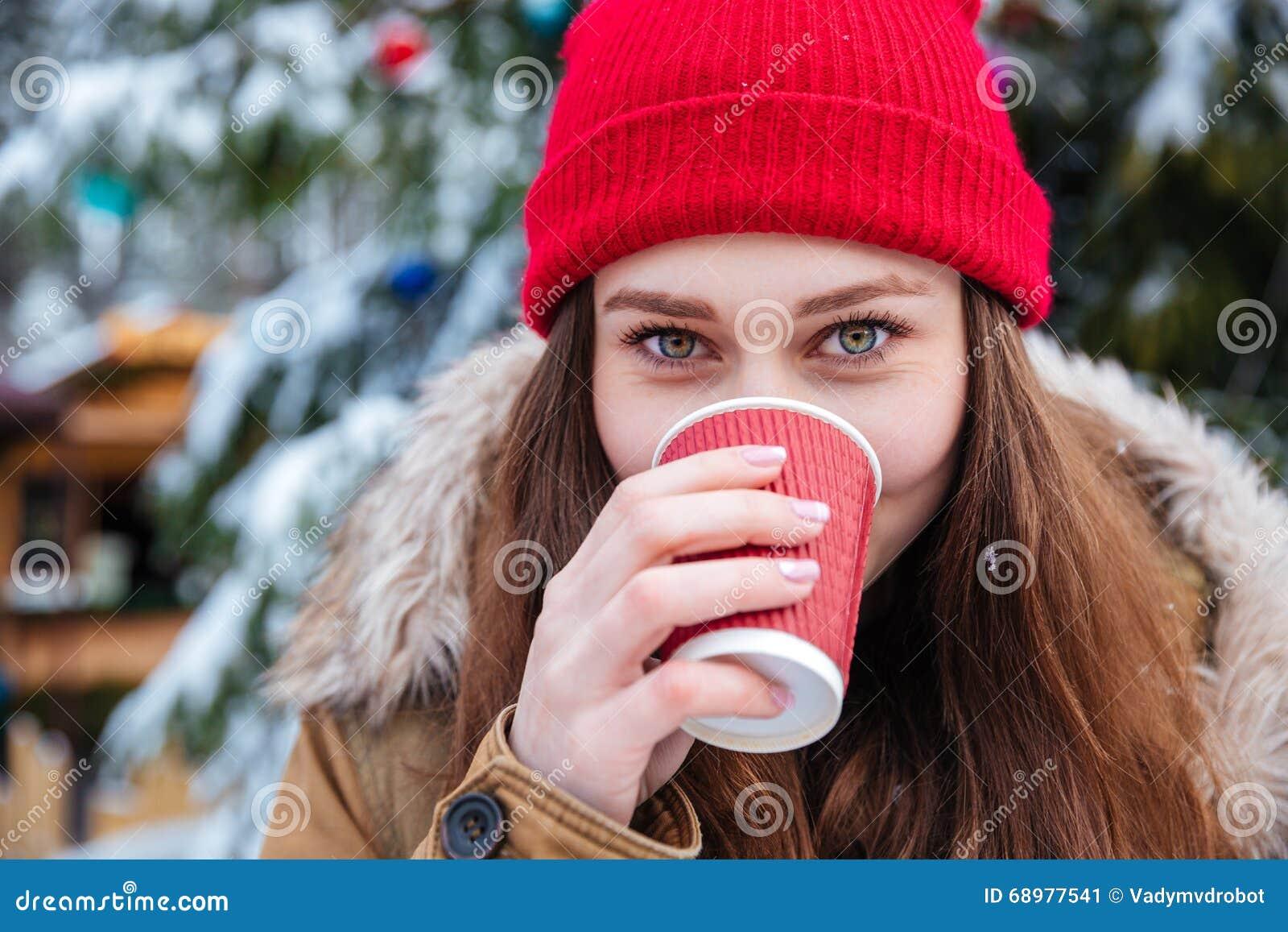 Nette Frau, die draußen heißen Kaffee im Winter trinkt