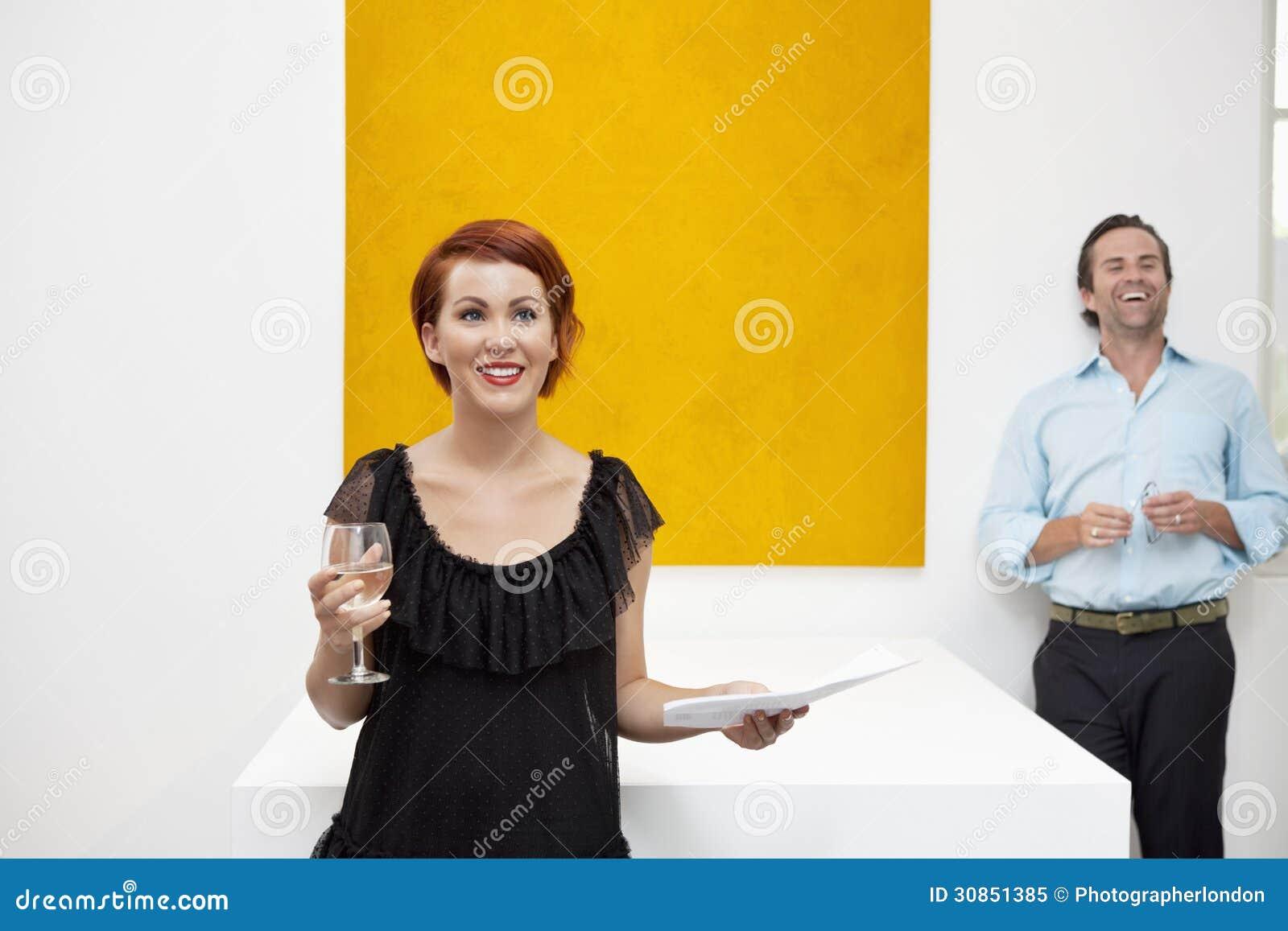 Nette Frau, Die Vor Gelber Malerei Mit Mann Im Hintergrund