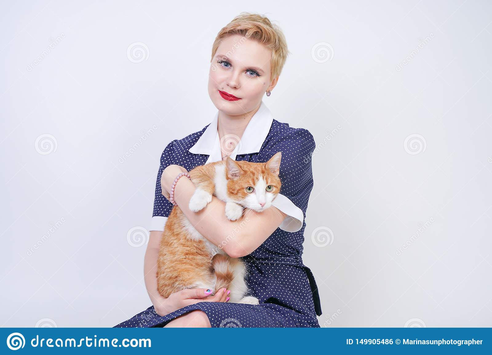 Nette nette Frau mit dem kurzen Haar im Pinuptupfenkleid, das ihr geliebtes Haustier auf einem weißen Hintergrund im Studio hält